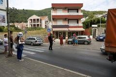 El policía dirige tráfico en el paso de peatones Budva, Montenegro Foto de archivo