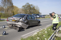 El policía toma las imágenes, imágenes de un coche dañado Imagen de archivo libre de regalías