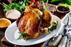 El pollo asado con romero sirvió en la placa blanca con las salsas en la tabla de madera, foco selectivo Fotos de archivo libres de regalías