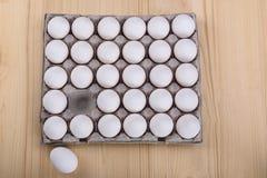 El pollo blanco eggs en un paquete de la cartulina, uno está en fondo imagen de archivo