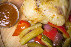 El pollo con las verduras sirvió en tabla de cortar redonda en quemado Foto de archivo
