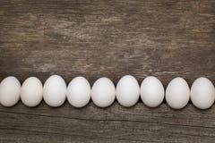 El pollo eggs en fila en la tabla rústica de madera Visión superior, endecha plana Imágenes de archivo libres de regalías