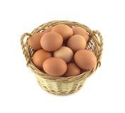 El pollo eggs en la cesta de mimbre aislada en el primer blanco Foto de archivo