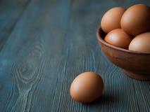 El pollo eggs en un pote de arcilla en fondo de madera oscuro Fotografía de archivo