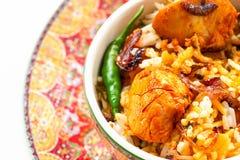 El pollo indio Halal Biryani sirvi? con raita del tomate del yogur sobre el fondo blanco Foco selectivo imagen de archivo