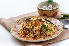 El pollo indio Halal Biryani sirvi? con raita del tomate del yogur sobre el fondo blanco Foco selectivo imágenes de archivo libres de regalías