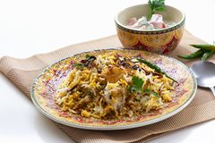 El pollo indio Halal Biryani sirvi? con raita del tomate del yogur sobre el fondo blanco Foco selectivo fotografía de archivo libre de regalías