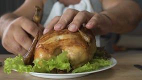 El pollo masculino gordo solo de la consumición con las manos, malas maneras, hambriento muerto de hambre escoge almacen de video