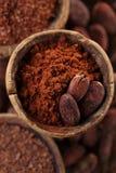 El polvo de cacao y los granos de cacao asados en cuchara vieja cucharean el backgr Imagen de archivo libre de regalías