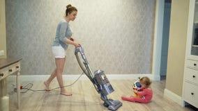 El polvo limpio de la madre del piso con un aspirador y una hija del ` s del pequeño niño están jugando cerca almacen de metraje de vídeo