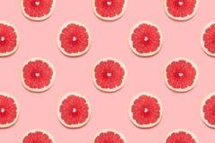 El pomelo corta el modelo inconsútil tropical en concepto mínimo del verano del fondo del rosa foto de archivo