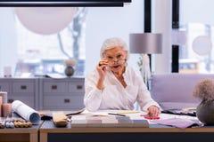 El poner de envejecimiento atractivo del empresario de vidrios mientras que se sienta en silla foto de archivo
