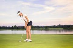 El poner del golfista de la muchacha. fotografía de archivo