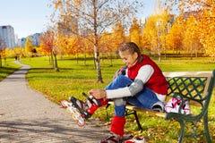 El poner en patines en el banco en el parque Fotos de archivo