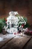 El poner letras de la Feliz Año Nuevo de la Feliz Navidad Defocused Imagen de archivo libre de regalías