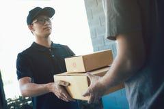 El portador asi?tico del cargo sostiene una caja de cart?n con el interior del paquete y el beneficiario est? firmando el paquete imagenes de archivo