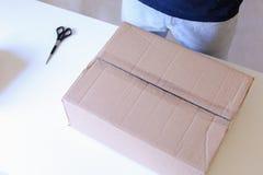 El portador comprueba las cajas llenas, selladas con la cinta por todos los lados, vuelta Imagenes de archivo