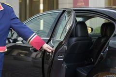 El portero abre la puerta de un coche de lujo Fotografía de archivo libre de regalías