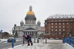 El portero del habitante del sur limpia nieve cerca de la cátedra del St Isaac Fotografía de archivo