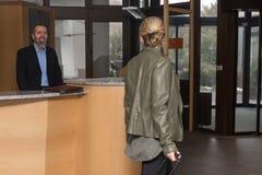 El portero en un hotel smilling a una huésped femenina foto de archivo libre de regalías