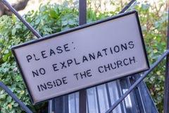 El poste indicador con palabras señaliza 'por favor: Ningunas explicaciones dentro de la iglesia ' fotos de archivo
