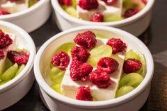 El postre blanco rueda con queso del ` s del pío, uvas verdes y rasperries rojos antes de asar a la parrilla en el horno Imagenes de archivo