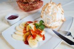 El postre con los plátanos y el kiwi en fresa sauce Foto de archivo libre de regalías