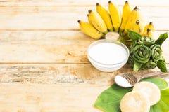 El postre de plátanos maduros tiene materia prima de la naturaleza tal como leche de coco y azúcar y sal en fondo de madera Visió Imagen de archivo libre de regalías