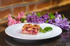 El postre elegante, empanada de la fruta, en el fondo florece Foto de archivo libre de regalías