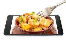 El pote con los pedazos fritos listos de carne del pollo y de una bifurcación que va fuera de la pantalla del smartphone aisló en Foto de archivo libre de regalías