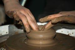 El pote de arcilla se hace las manos de los niños Imagen de archivo