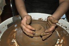 El pote de arcilla se hace las manos de los niños Imagenes de archivo