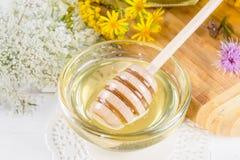El pote de cristal lleno de miel líquida fresca y la miel se pegan con las flores salvajes del verano Fotografía de archivo