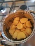 El pote del hierro, patatas peladas, la estufa de gas imagen de archivo libre de regalías