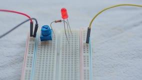 El potenci?metro, los resistores y el LED rojo pusieron en una tabla de cortar el pan imagen de archivo libre de regalías