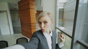 El POV de la empresaria joven en el traje que toma una foto del selfie que sostiene smartphone y se divierte en oficina moderna