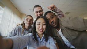 El POV de la muchacha asiática que sostiene el smartphone que toma las fotos del selfie con los compañeros de clase multi-étnicos metrajes