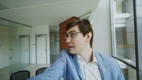 El POV del hombre de negocios alegre joven en los vidrios que toman una foto del selfie y se divierte en oficina moderna metrajes