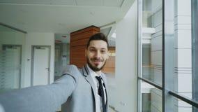 El POV del hombre de negocios joven en el traje que toma una foto del selfie y se divierte en oficina moderna