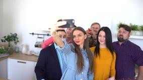El POV del hombre joven con los amigos que toman la foto del selfie en cámara del smartphone y se divierte en casa dentro metrajes