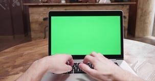 El POV tiró de la persona que trabajaba en un ordenador portátil moderno con la pantalla verde almacen de metraje de vídeo