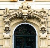 El pozo adornó la puerta exterior con tres caras y elementos florales Imágenes de archivo libres de regalías