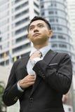 El pozo vistió al hombre de negocios asiático que ajustaba su corbata Imagen de archivo