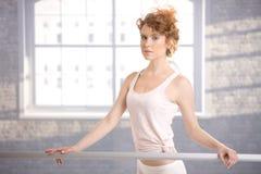 El practicar de la barra de la muchacha bonita de la bailarina que hace una pausa Imagen de archivo libre de regalías