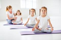 El practicar de los niños enganchó a gimnasia y a yoga con el profesor Imágenes de archivo libres de regalías