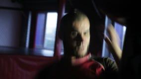 El practicar del hombre golpea el gimnasio con el pie adentro de encajonamiento Luchas sin reglas MMA almacen de metraje de vídeo