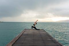 El practicar equilibrado forma de vida sana de la yoga de la mujer medita y energía en el puente por mañana foto de archivo libre de regalías