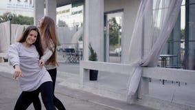 El practicar moderno de dos bailarines del jazz al aire libre por el edificio almacen de metraje de vídeo