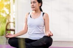 El practicar que se sienta de la mujer asi?tica hermosa haciendo la yoga que medita despu?s de despertar concepto en casa, sano y fotos de archivo