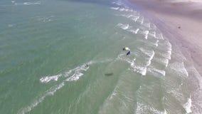 El practicar surf con los paracaídas en el mar almacen de metraje de vídeo